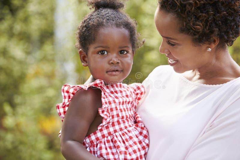 拿着小女儿的非裔美国人的母亲画象 免版税库存图片