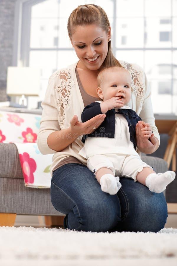 拿着小女婴的年轻母亲 免版税图库摄影