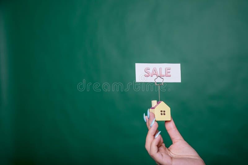 拿着小屋的女商人 提出房子的一个小模式的手隔绝在绿色背景待售 免版税库存照片