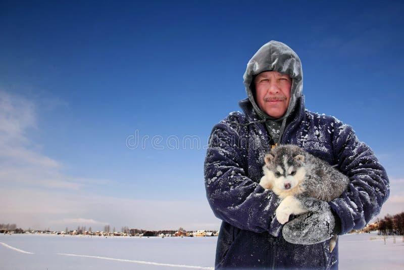 拿着小狗的人在冬天 免版税库存图片