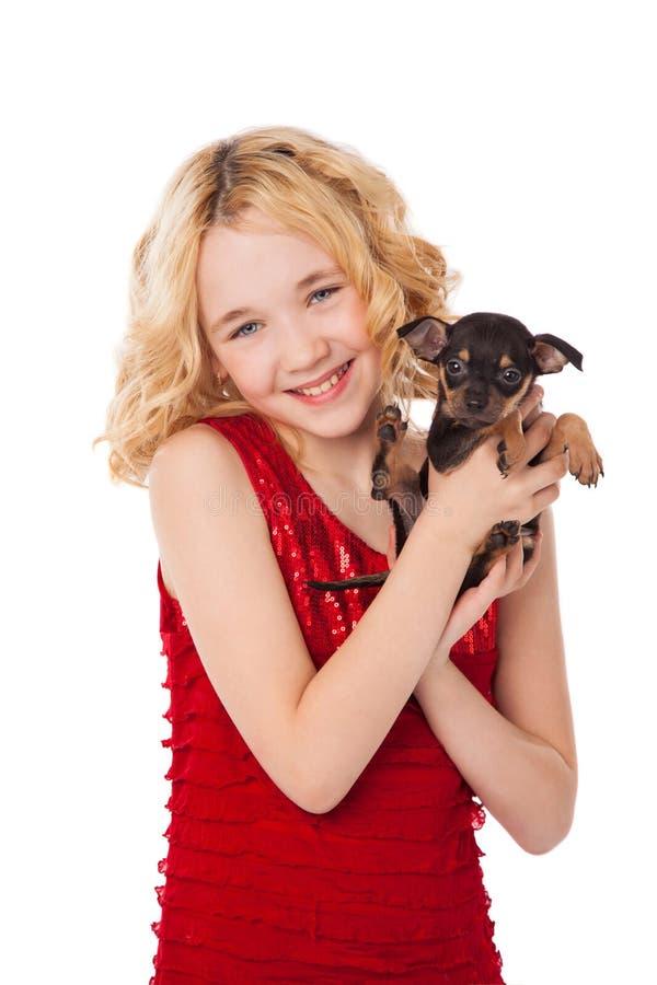 拿着小狗的白肤金发的小女孩穿红色礼服 免版税库存照片