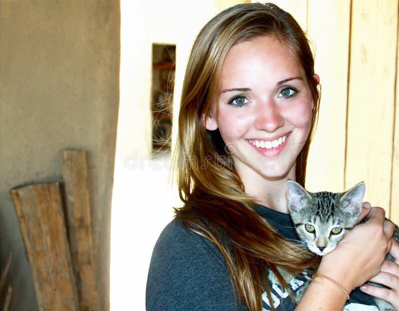 拿着小猫的特写镜头微笑的青少年的女孩 免版税库存图片