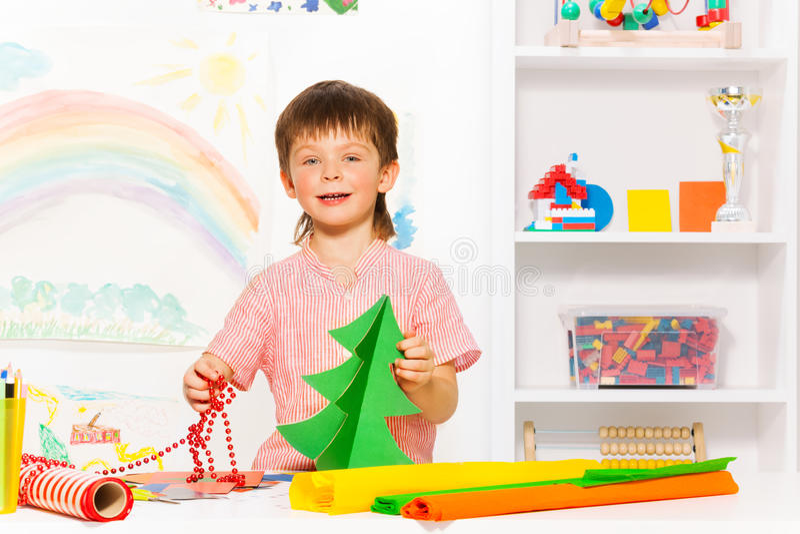 拿着小珠和纸盒Xmas树的愉快的男孩 库存照片