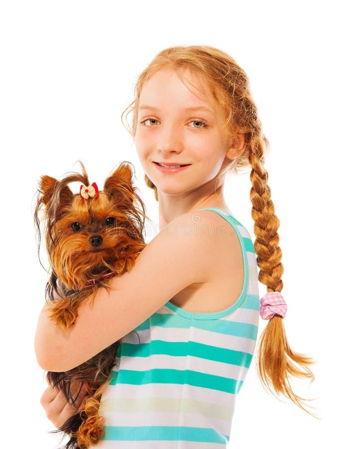 拿着小的逗人喜爱的狗的严肃的微笑的女孩 免版税库存图片