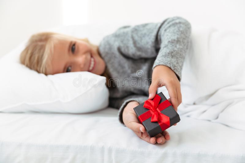 拿着小礼物盒的愉快的小女孩,当在床, sel上时 免版税库存照片