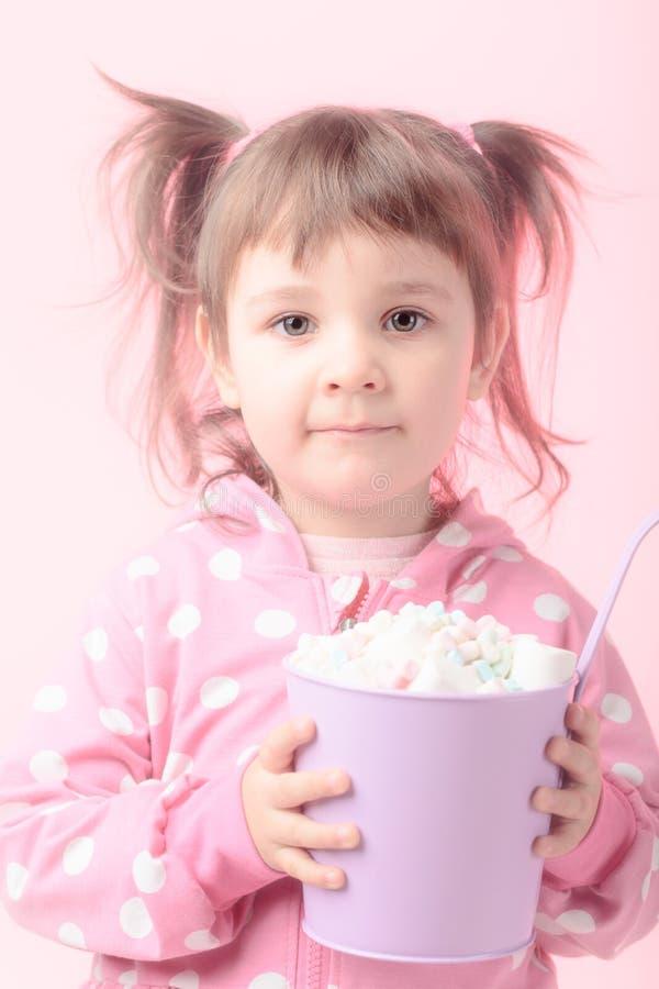 拿着小紫罗兰色桶蛋白软糖的逗人喜爱的小女孩 图库摄影