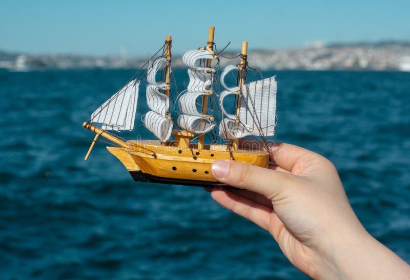 拿着小船模型,海的儿童手在背景中 免版税库存照片
