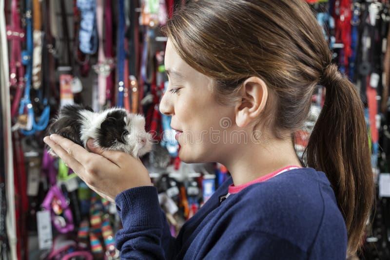 拿着小试验品的逗人喜爱的女孩在商店 免版税图库摄影