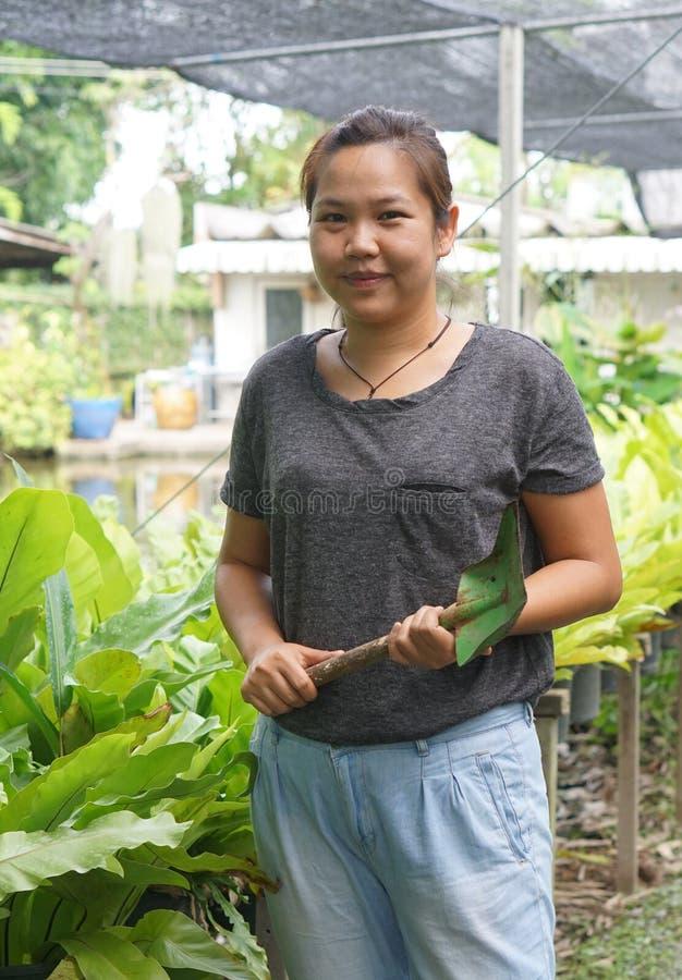 拿着小铁锹和微笑对她的pla的亚裔妇女花匠 库存图片