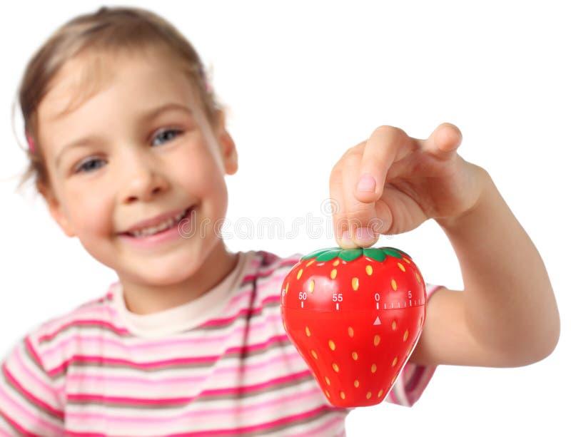 拿着少许形状草莓定时器的女孩 免版税库存照片