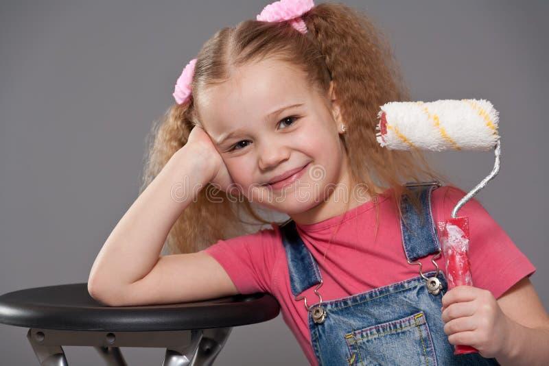 拿着少许漆滚筒的女孩 免版税库存图片
