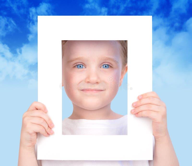 拿着少许照片的男孩逗人喜爱的框架 免版税库存照片