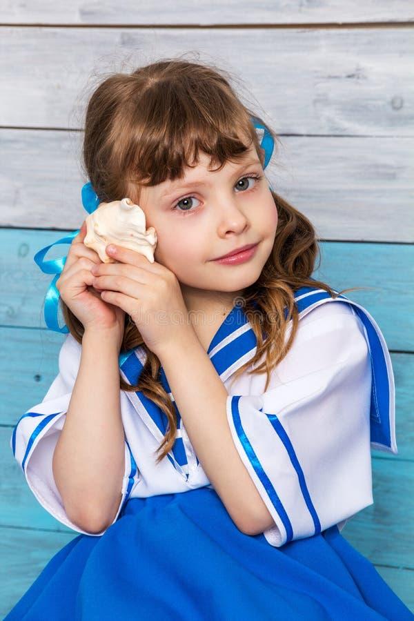 拿着少许贝壳的女孩 免版税库存照片