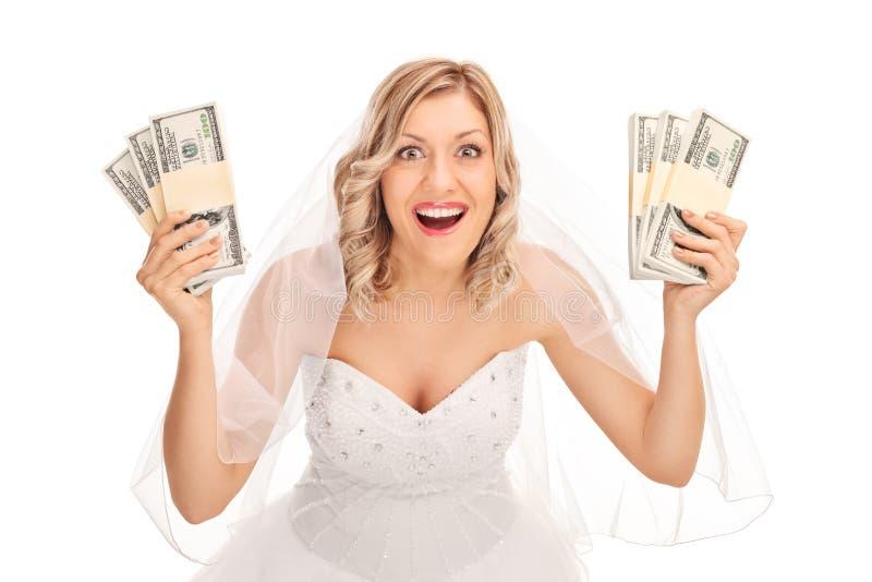 拿着少量堆金钱的年轻新娘 免版税库存照片