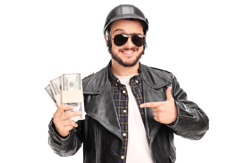 拿着少量堆金钱的年轻男性骑自行车的人 图库摄影