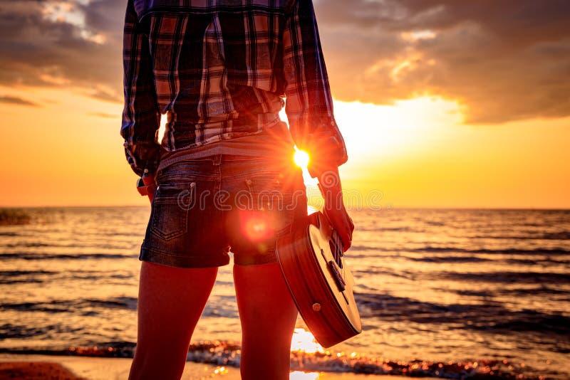 拿着尤克里里琴的日落的妇女 免版税库存照片