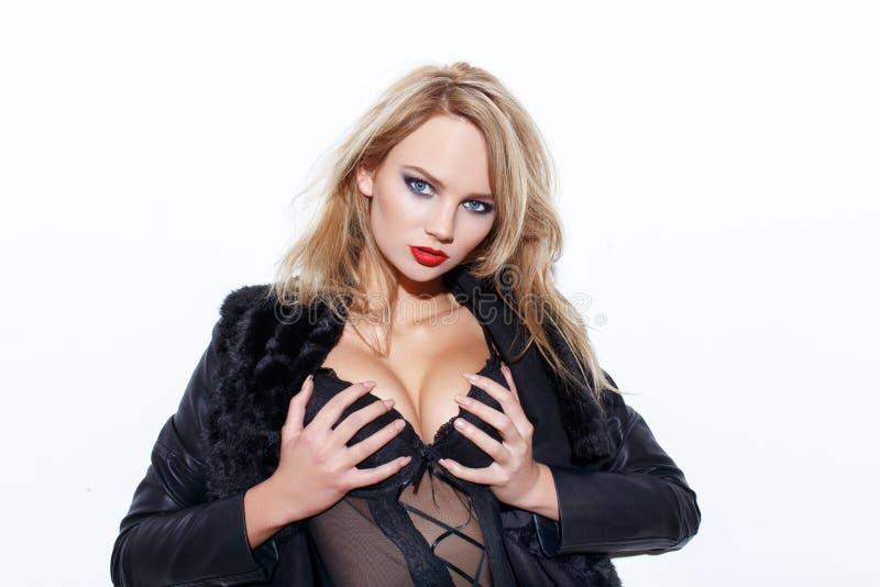 拿着山雀的肉欲的白肤金发的妇女 免版税库存图片