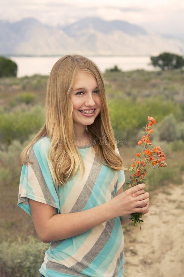 拿着巢的愉快的十几岁的女孩外面 库存照片