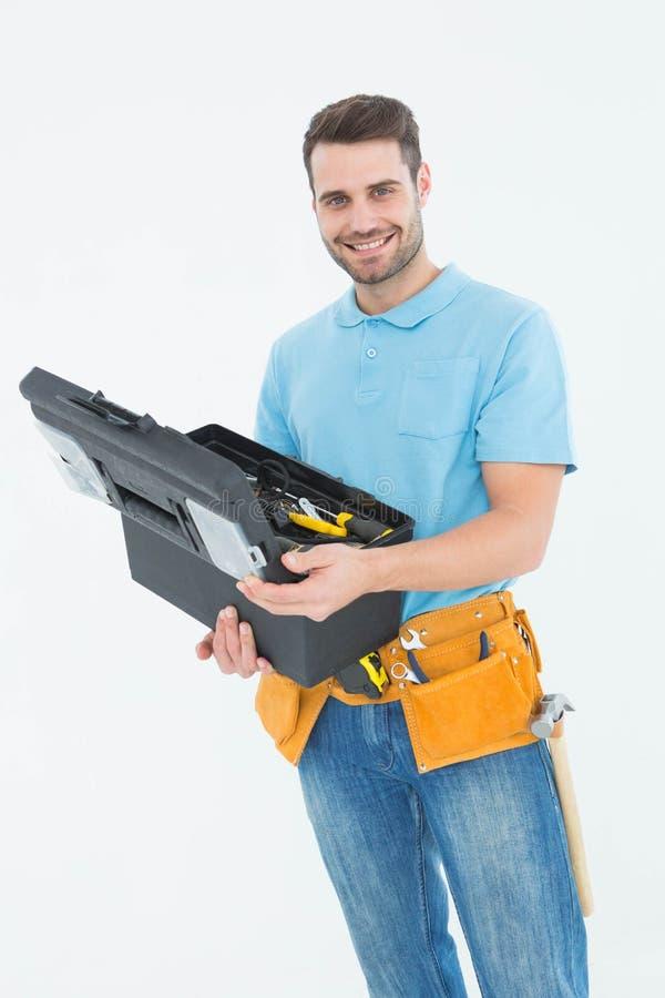 拿着工具箱的愉快的建筑工人 免版税库存图片