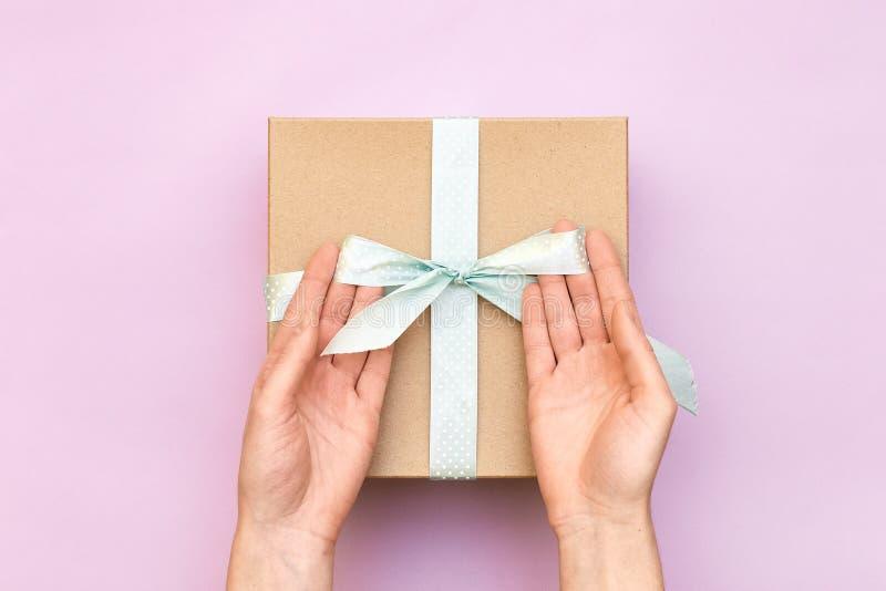 拿着工艺有蓝色弓的妇女手礼物盒在粉红彩笔背景 女孩束缚当前箱子的经典弓 顶视图,平 库存照片