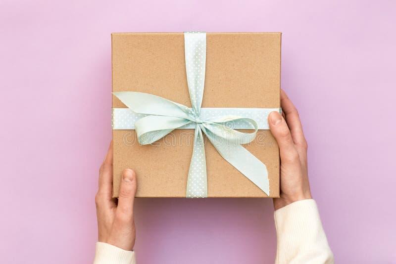 拿着工艺有蓝色弓的妇女手礼物盒在粉红彩笔背景 女孩束缚当前箱子的经典弓 顶视图,平 免版税图库摄影