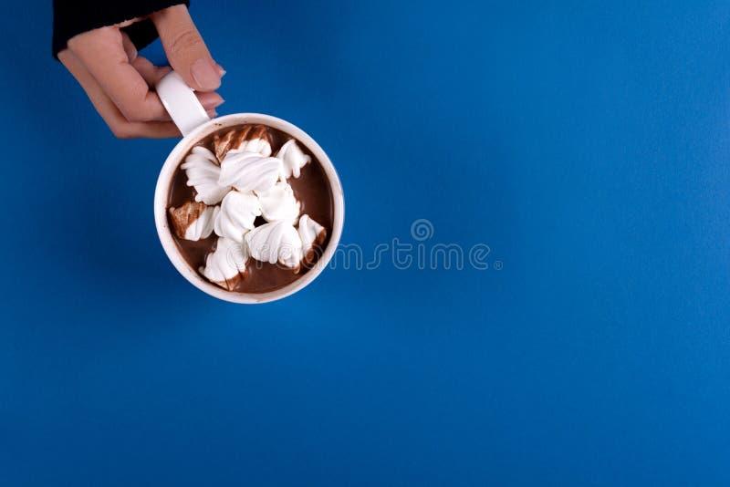 拿着巧克力热饮用在蓝纸背景的蛋白软糖糖果的女性手 顶视图 免版税图库摄影