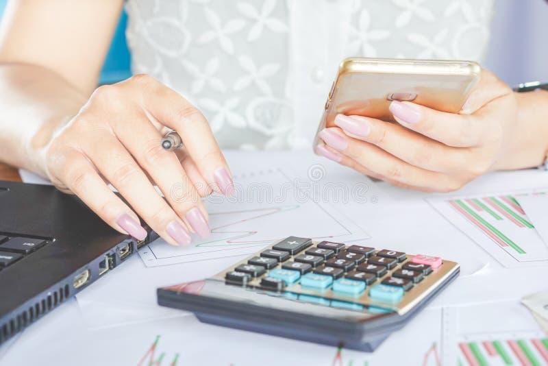 拿着巧妙的电话和研究财政图表报告的女实业家手 免版税库存图片