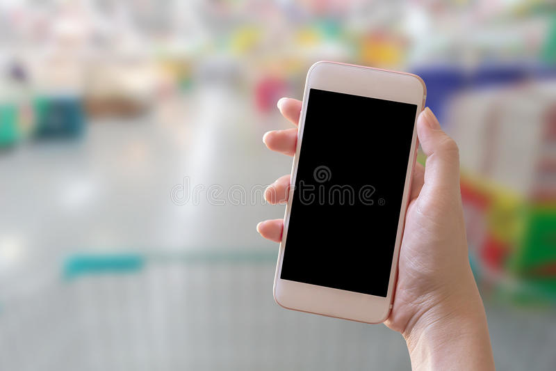 拿着巧妙的电话有迷离背景的手 库存图片