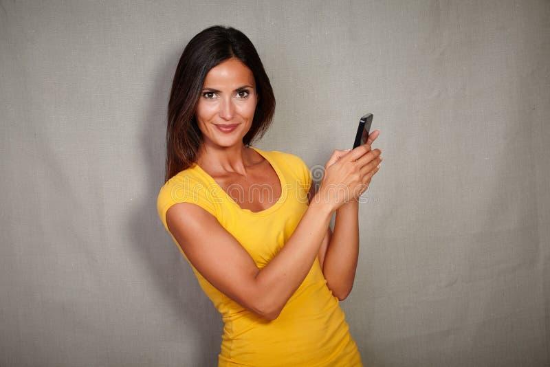 拿着巧妙的电话的吸引人少妇 库存照片