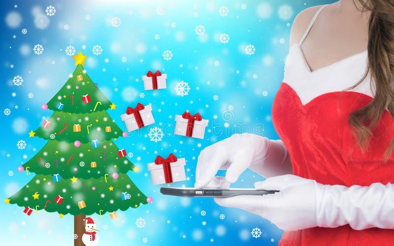 拿着巧妙的电话的圣诞节妇女送了圣诞节礼物 免版税库存照片