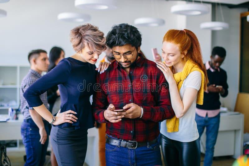 拿着巧妙的电话的巧妙的便衣的确信的年轻印地安人 库存图片
