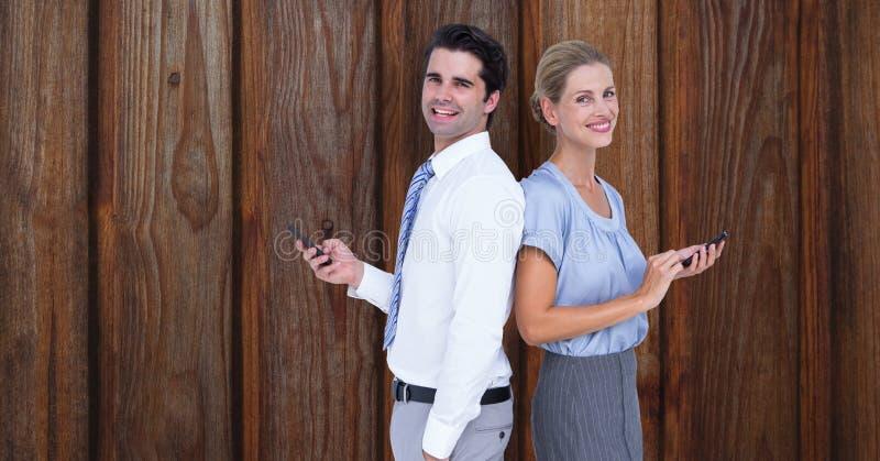 拿着巧妙的电话的微笑的商人,当紧接站立对木墙壁时 库存例证
