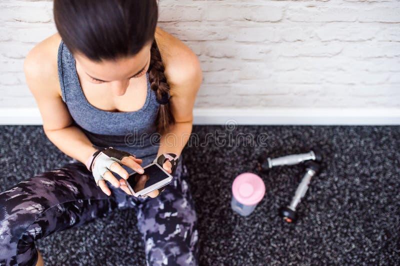 拿着巧妙的电话,砖墙的健身房的适合的妇女 库存照片