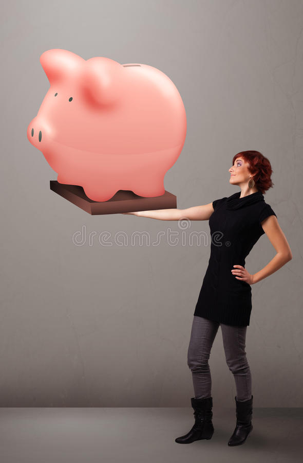 拿着巨大的储款存钱罐的女孩 图库摄影