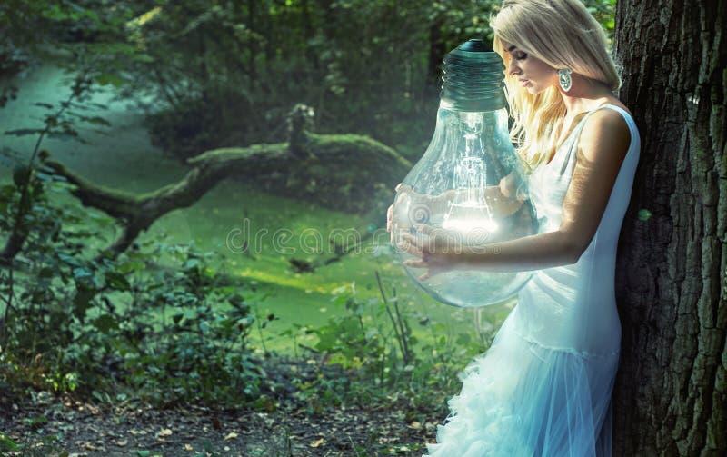 拿着巨大的电灯泡的惊人的白肤金发的夫人 免版税库存照片
