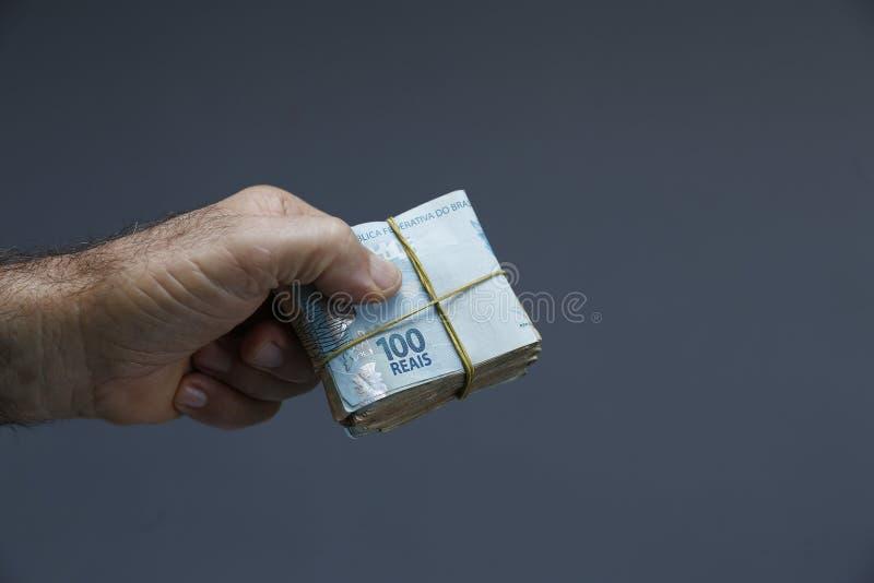 拿着巴西真正的笔记-从巴西的金钱的手-笔记真正-巴西BRL钞票 图库摄影