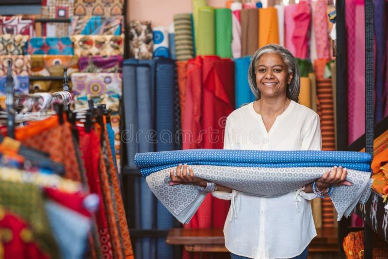 拿着布料卷的微笑的成熟妇女在她的织品商店 免版税库存照片