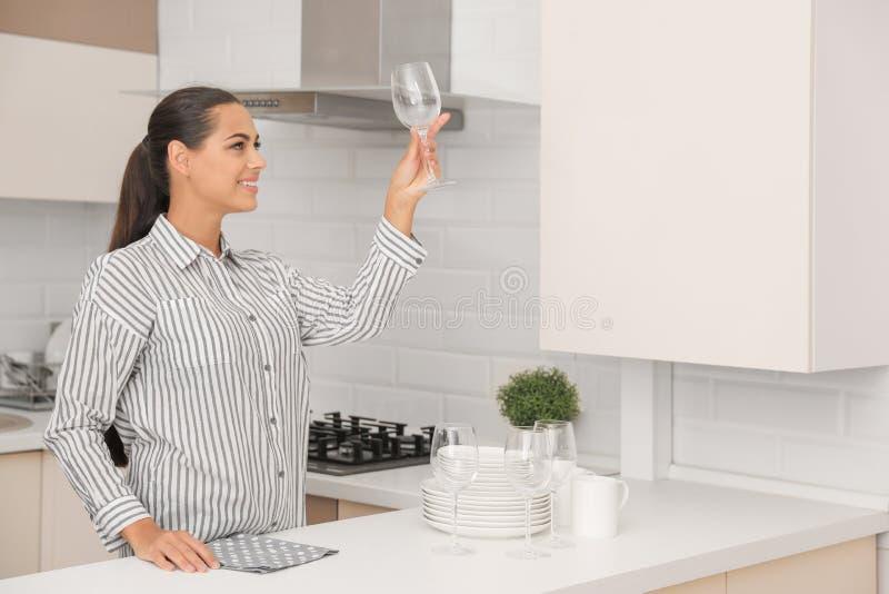 拿着干净的玻璃的年轻女人在厨房里 库存图片