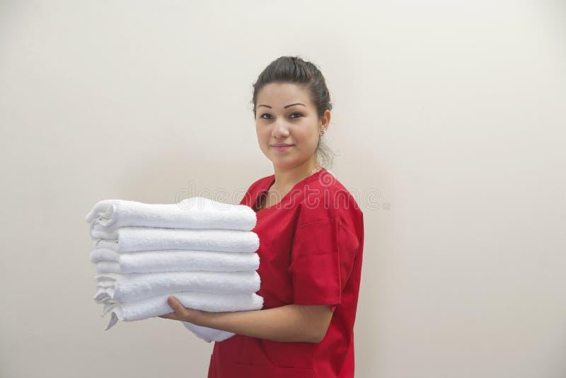 拿着干净的白色毛巾的女性管家画象反对灰色背景 库存图片