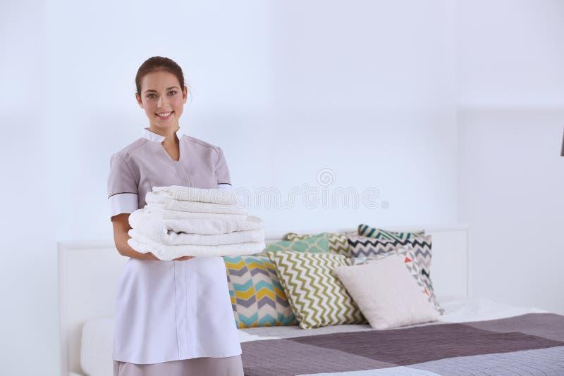 拿着干净的白色被折叠的毛巾的女性女服务生 图库摄影