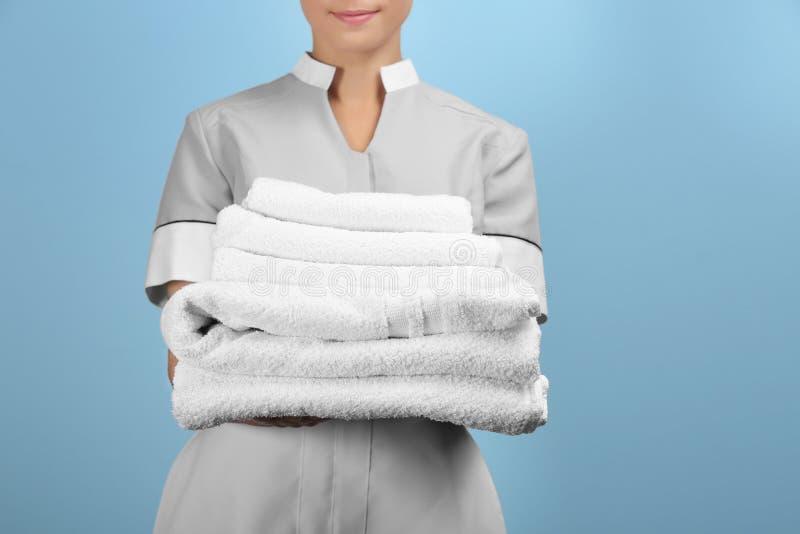 拿着干净的白色被折叠的毛巾的女性女服务生 免版税库存照片