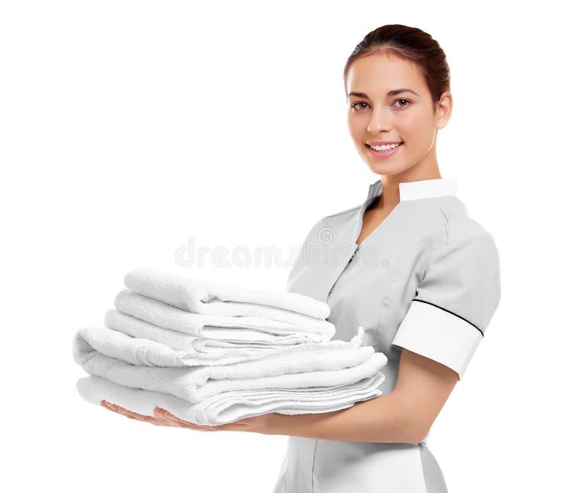 拿着干净的白色被折叠的毛巾的女性女服务生 库存照片