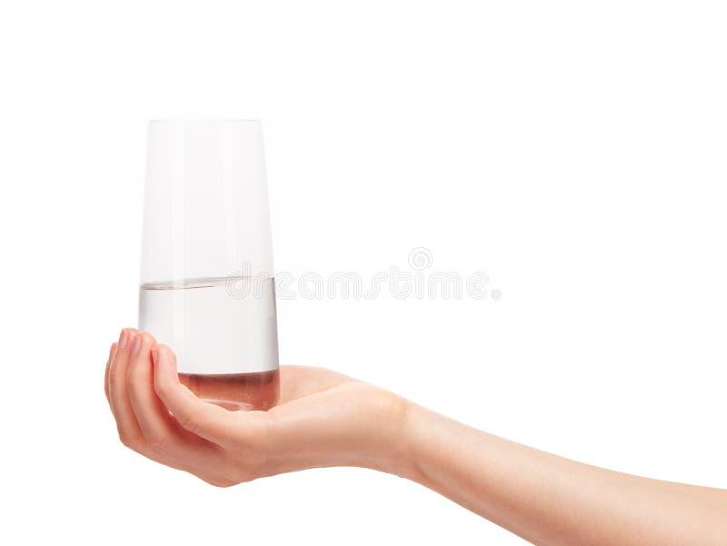 拿着干净的水杯用水的女性手 免版税库存图片