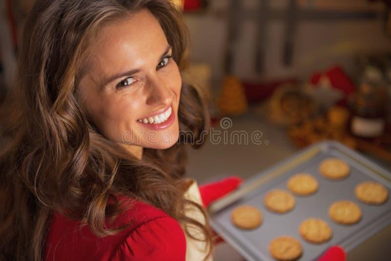 拿着平底锅用圣诞节曲奇饼的主妇画象 库存图片