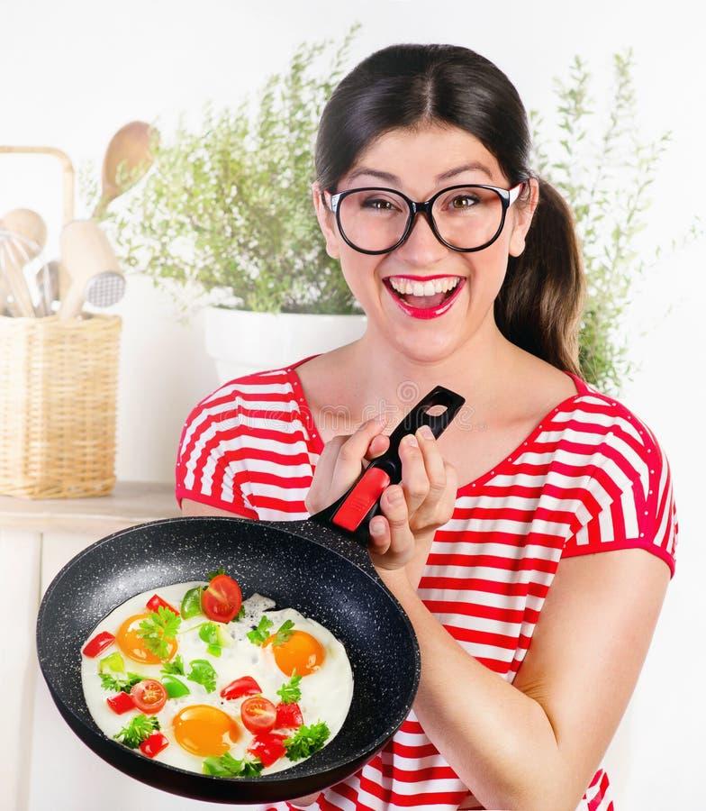拿着平底锅用鸡蛋的年轻滑稽的愉快的妇女 免版税库存图片