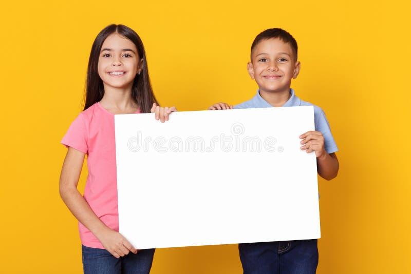 拿着广告的男孩和女孩空的委员会 免版税库存图片