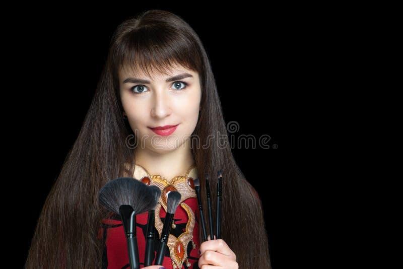 拿着应用的年轻美女化妆用品刷子 免版税库存图片