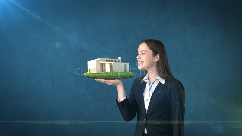 拿着开放手棕榈的少妇画象现代房子,在被隔绝的演播室背景 到达天空的企业概念金黄回归键所有权 库存图片