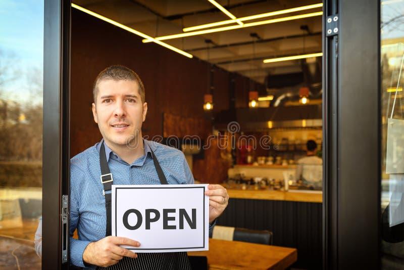 拿着开放标志-新的小家庭餐馆邀请的pe入口的年轻人企业家的愉快的企业主画象  免版税图库摄影