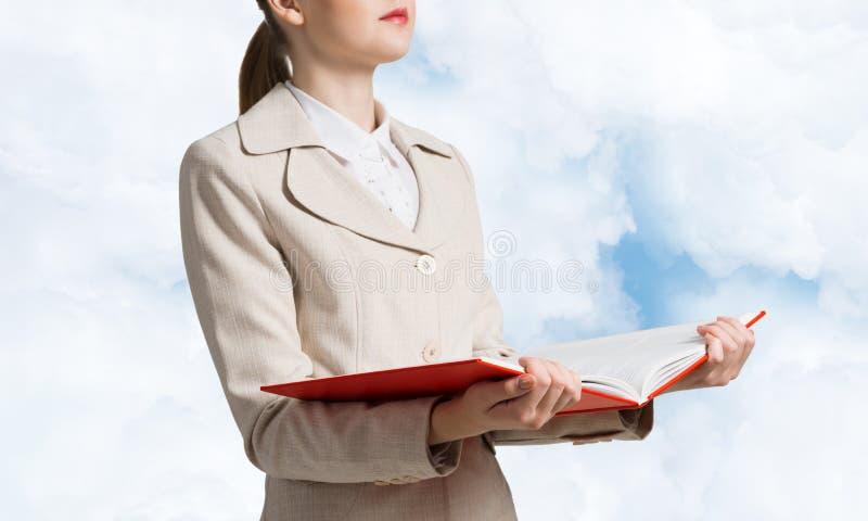 拿着开放笔记本的女商人 库存照片